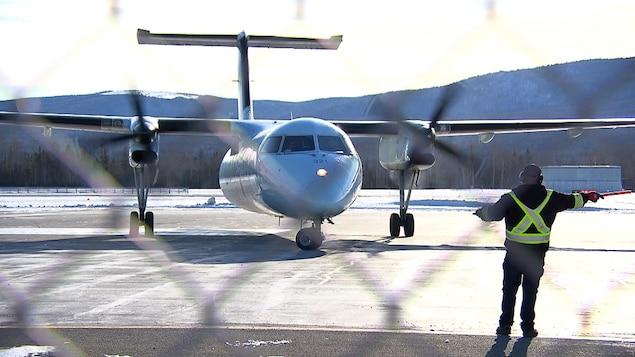 Un agent de piste fait circuler un avion sur la piste de l'aéroport de Gaspé.
