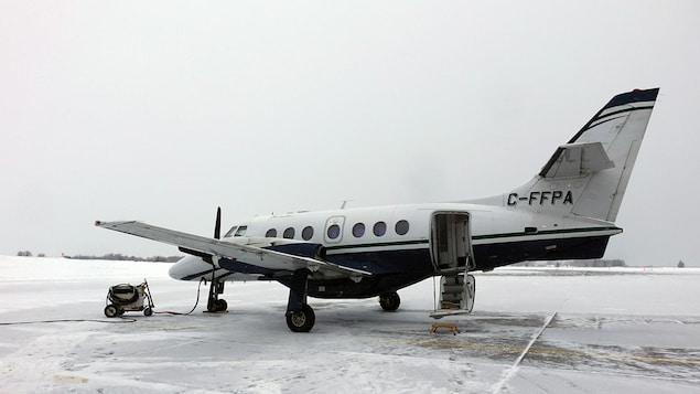 Une Port-Cartoise demande une révision des horaires de vols vers Québec Un petit avion est posé sur la piste d'atterrissage en hiver.