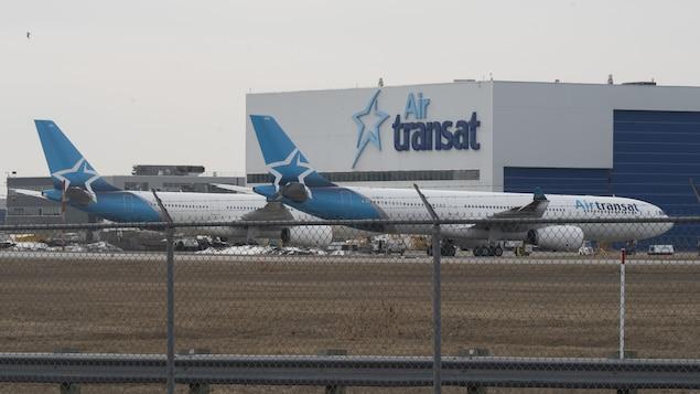 Un bâtiment d'Air Transat et deux avions au sol.