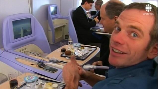 Le chanteur Garou, souriant, assis dans son siège d'avion avec écran montrant le ciel en vol.