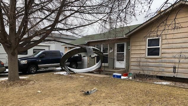 Un gros débris d'avion devant une maison