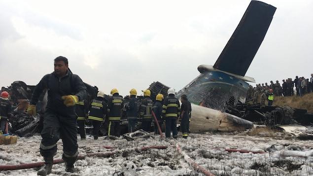 Des secouristes près de l'épave d'un avion.