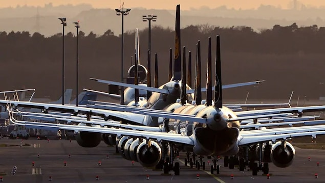 Plusieurs avions alignés sur la piste d'un aéroport.