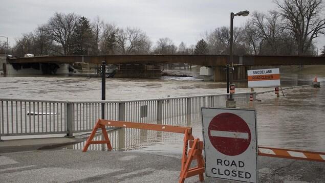Une route qui longe une rivière est fermée et inondée.