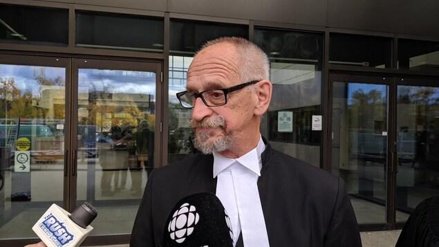Un avocat répond aux questions de journalistes.
