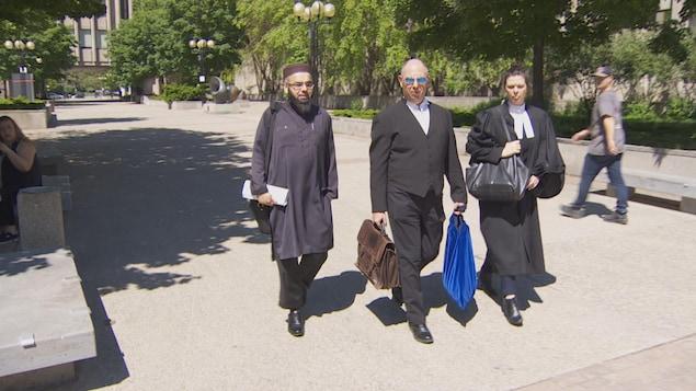 Omar Kalair et ses avocats, dont Edward Prutschi au centre, marchent dans la rue.