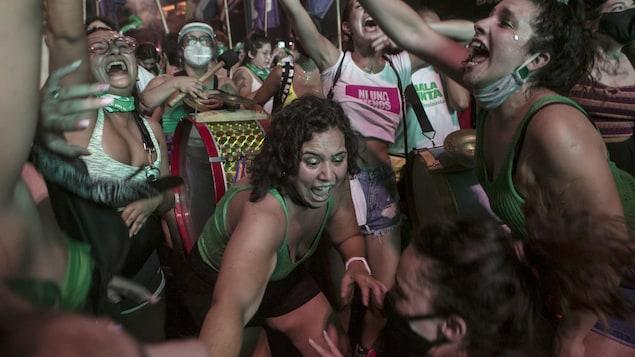 Des dizaines de femmes habillées de vert manifestent leur joie.