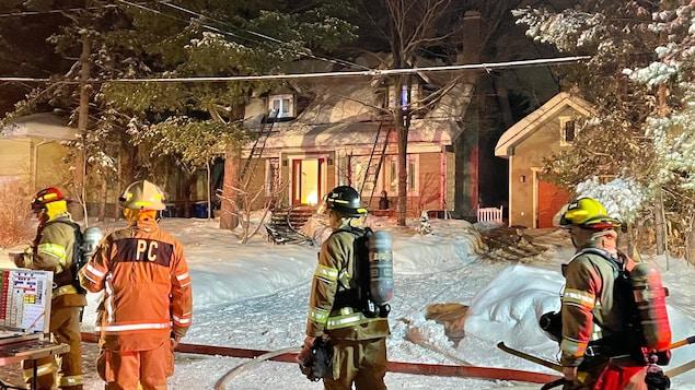 Quatre pompiers devant une résidence où des flammes sont visibles.