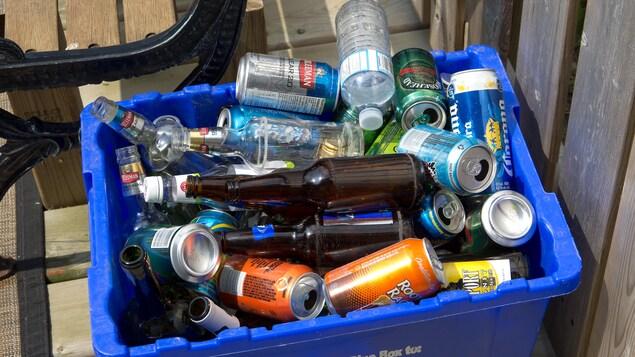 Un bac de recyclage rempli de bouteilles et de canettes.