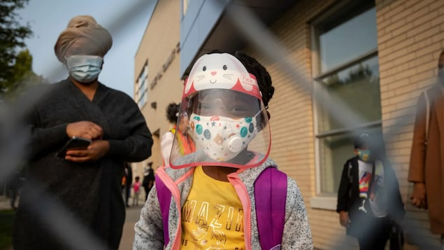 A Toronto elementary school student wears full PPE before heading into class last September. Students will continue to wear masks inside classrooms as part of Ontario's new plan.