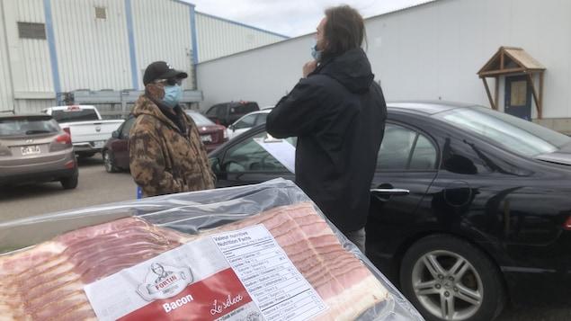 Deux hommes parlent dans un stationnement derrière un paquet de bacon en gros plan.