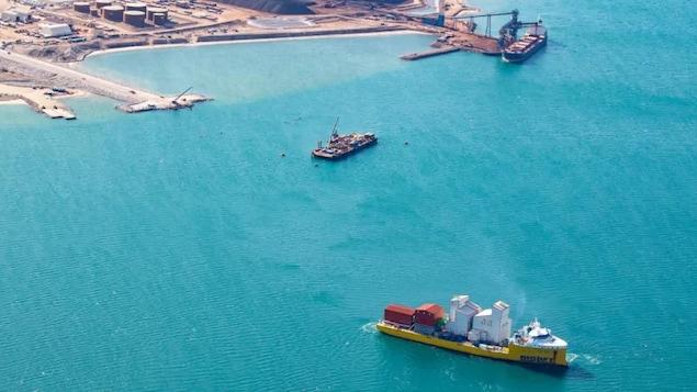 Un bateau-cargo transporte des équipements près du quai la mine.