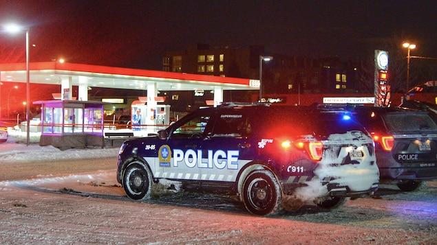 Un véhicule de police du SPVM est stationné à côté d'un périmètre de sécurité devant une station-service.