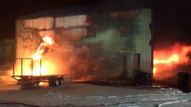 Des flammes sortent par les portes de l'usine en pleine nui