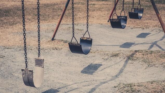 Balançoires inutilisées dans un terrain de jeux.