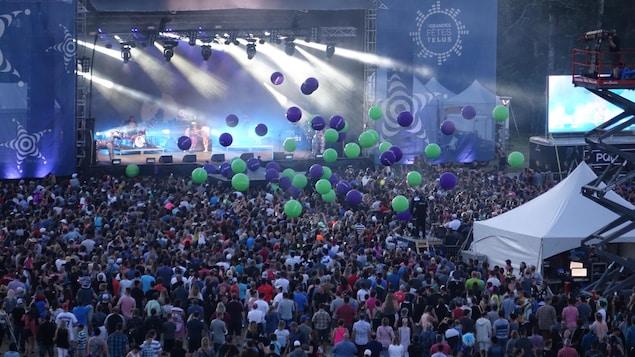 Des ballons naviguent au dessus d'une foule de personnes qui assistent à un spectacle extérieur. On voit une grande scène avec des projecteurs de lumière.
