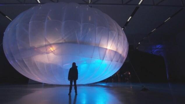 Le gros ballon gonflé a la forme d'une citrouille. Devant se tient une personne.