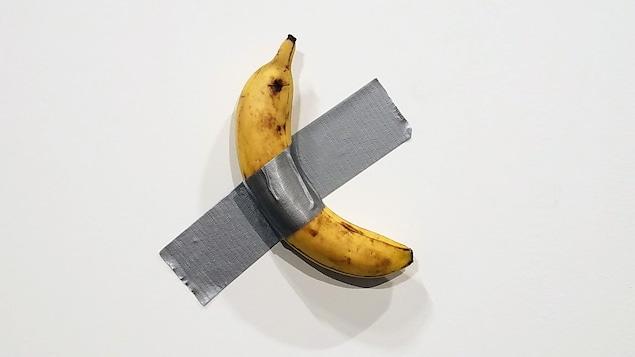 Une banane collée sur un mur avec du ruban adhésif en toile gris.