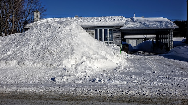 Un banc de neige atteint le toit d'une maison.