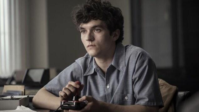 un jeune homme joue seul à un jeu vidéo avec une manette.