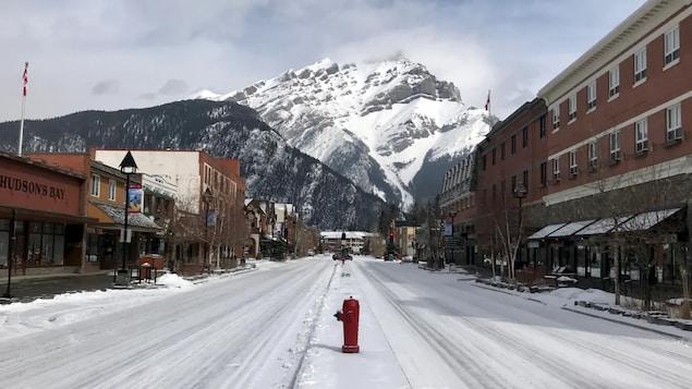 Les rues de Banff désertes avec les montagnes enneigées en arrière plan.