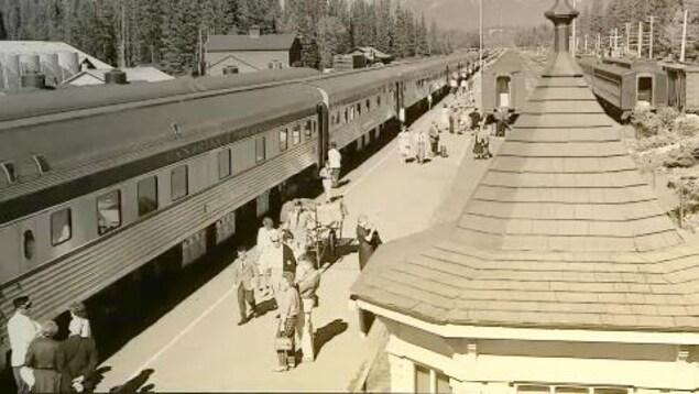 Sur cette photo en sépia, des passagers se tiennent sur une plateforme de train. Un train composé de nouveaux wagons en métal y est arrêté.