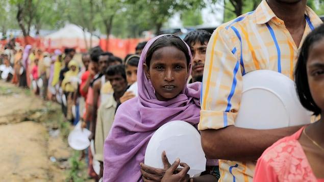 Des réfugiés rohingyas font la queue pour recevoir de la nourriture dans un camp installé au Bangladesh.