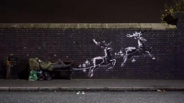 Deux rennes peints en blanc tirent un banc sur lequel est allongé un sans-abri.