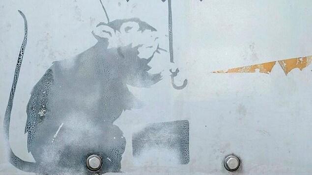 Graffiti d'un rat tenant un parapluie.
