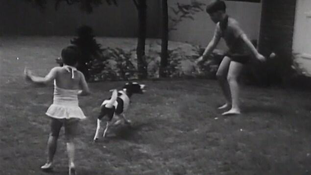 Fillette et garçon qui jouent avec leur chien dans la cour.