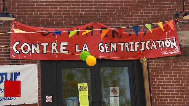 Une bannière au-dessus d'une porte, sur laquelle il est écrit : « Contre la gentrification ».