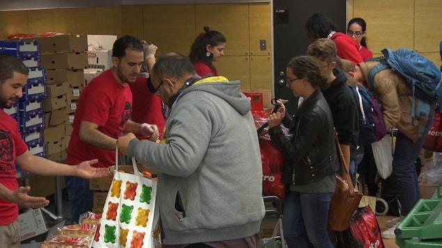 Des étudiants se procurent des denrées dans une banque alimentaire.