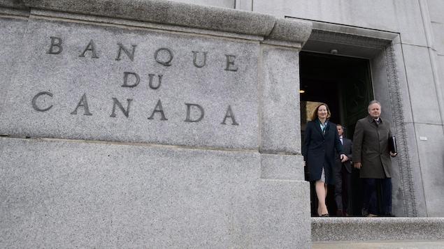 Stephen Poloz, gouverneur de la Banque du Canada et Carolyn Wilkins, première sous-gouverneure, sortent en souriant d'un immeuble sur lequel il est inscrit « Banque du Canada ».