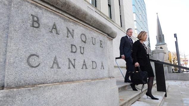 Stephen Poloz et Carolyn Wilkins descendent des marches devant l'immeuble de la Banque du Canada.