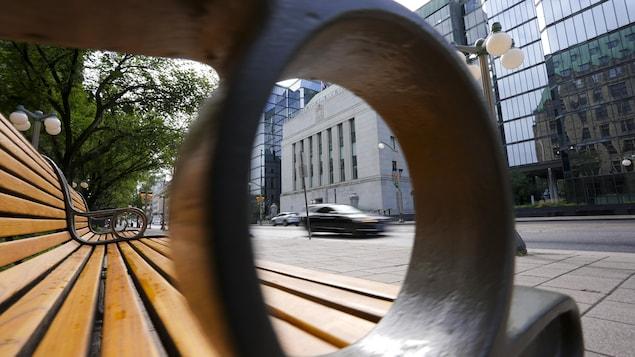 La Banque du Canada, vu à travers l'appui-bras d'un banc public.