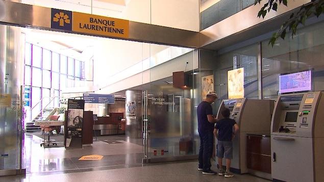 Un homme et un enfant se tiennent devant un guichet automatique situé à l'entrée d'une succursale de la Banque Laurentienne.