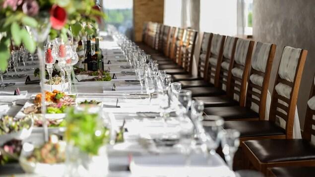 Une longue table de banquet avec ses couverts et de nombreuses chaises alignées les unes contre les autres.
