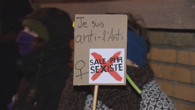 Une manifestante dénonce le bar l'Anti avec son affiche.