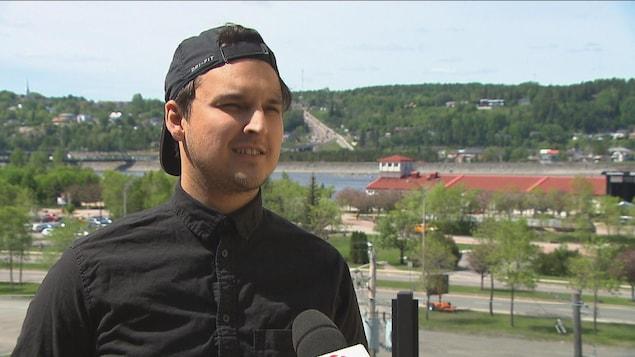 Un homme parle devant la zone portuaire.