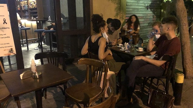 Cinq personnes assises à une table sur une terrasse.