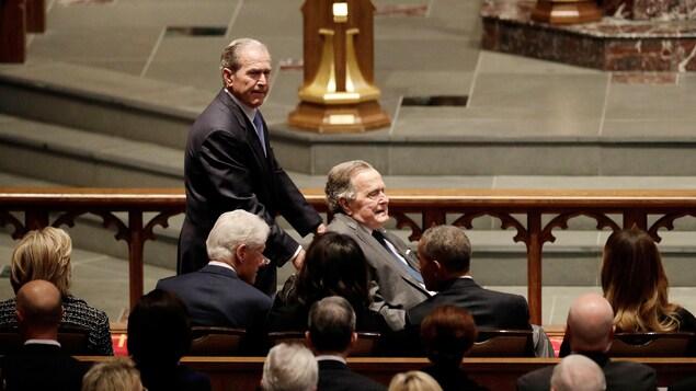 George W. Bush pousse le fauteuil roulant de son père; les cinq autres son assis et vus de dos.