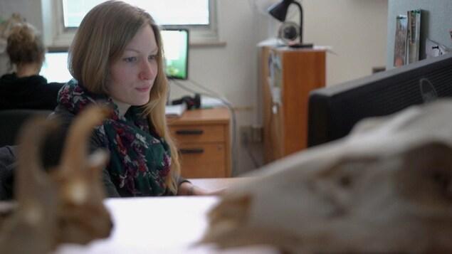 On voit Barbara Vuillaume assise à l'ordinateur, de profil.