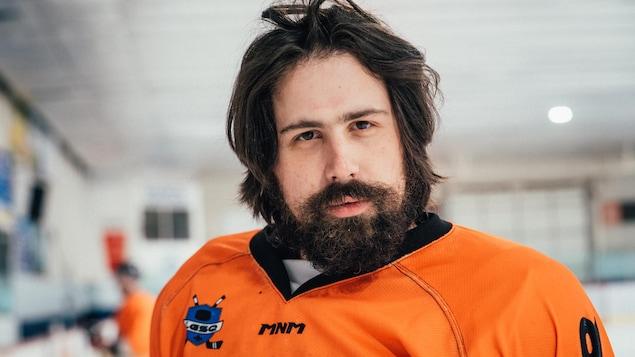 L'homme a une barbe fournie et un chandail de hockey orange vif.