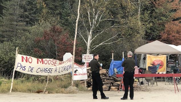 Des policiers discutent devant un barrage érigé par des communautés autochtones.