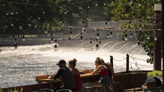 Deux couples sont assis à une terrasse devant le barrage de déversoir de l'île des Moulins.