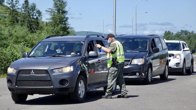 Un agent au point de contrôle discute avec un automobiliste dans une file d'attente.