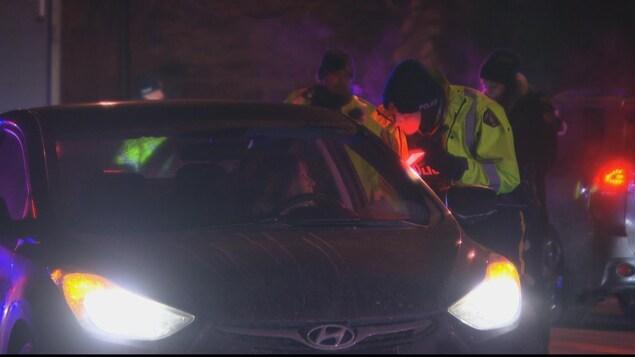 Un policier parle à une conductrice arrêtée dans un barrage routier à Ottawa