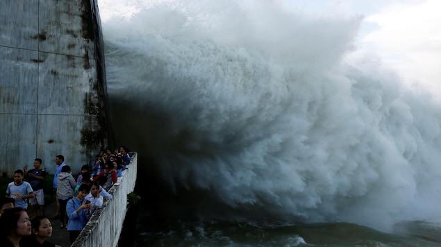 Des Vietnamiens sur un pont observent l'eau qui jaillit après l'ouverture des vannes.