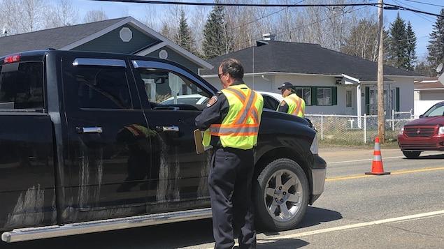Un pompier avec un dossard discute avec un automobiliste dans une camionnette.