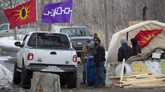 Cinq personnes se tiennent près de murets en béton et discutent avec le passager d'une camionnette blanche sur laquelle sont installés deux drapeaux.